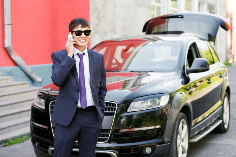 young-businessman-suit-sunglasses-talking-phone-next-to-expensive-car-outdoors-outside-68772535